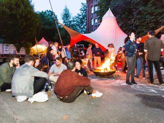 Besucher des Sommerfestes sitzen an am Feuer.